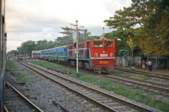 Passing a train on the Burmese Railway between Yangon and Mandalay, Myanmar. Another service passes the overnight express from Yangon to Mandalay Stock Photo