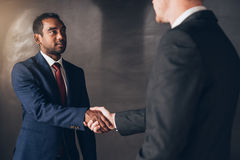 Another successful deal done. Two young businessmen standing in a modern boardroom shaking hands together after a successful negotiation Royalty Free Stock Photography