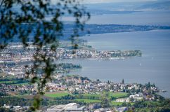 Another view from a hill down to the Bodensee. More parts of Switzerlland is shown, in front is a small blury tree Royalty Free Stock Image