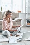 Another working day. Thoughtful young woman in eyewear working with documents while flooring at home stock photo