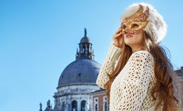 Woman looking into the distance while wearing Venetian mask Stock Photo