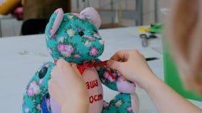 Anpassa kvinnan, toymakeren som binder pilbågen på hals av nallebjörnen Royaltyfri Fotografi