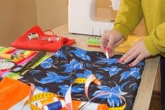 Anpassa Woman, modeformgivaren som arbetar på studion Cutting Fabric In för modeformgivare studio royaltyfri bild