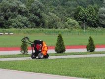 Anpassningar för omsorgen av gräsmattor av fotbollfält och stadion En maskin som gör det manuella arbetet av folk lättare Prepara arkivfoto