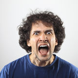 Anrgy and furious young man portrait. Anrgy and furious young man iin blue shirt portrait Royalty Free Stock Photo
