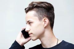Anrufe des jungen Mannes durch Handy Stockbild