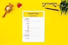 Ansökningsblankett för adopterar barnet på bästa sikt för gul bakgrund royaltyfria foton