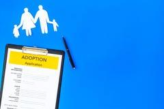 Ansökningsblankett för adopterar upp barnet på blå åtlöje för bästa sikt för bakgrund royaltyfri bild