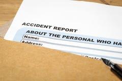 Ansökningsblankett och penna för olycksrapport på det bruna kuvertet, busi Royaltyfri Fotografi