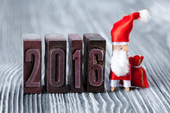 2016 ans écrit avec l'impression typographique colorée de vintage Concept de Noël - pince à linge Santa Claus avec un sac des cad Image stock