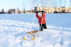 2 ans d'enfant dans la veste orange avec le traîneau en hiver Photos libres de droits