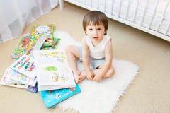 2 ans d'enfant en bas âge avec des livres dans sa chambre Images stock