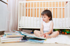 2 ans d'enfant en bas âge de livres de lecture contre le lit blanc Images stock