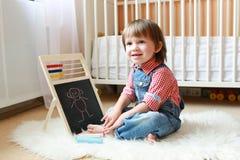 2 ans d'enfant en bas âge dessine sur le tableau noir avec la craie Image stock