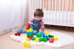 2 ans d'enfant en bas âge jouant le constructeur Photo libre de droits