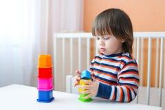 2 ans d'enfant en bas âge jouant le constructeur Photos libres de droits