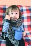 2 ans d'enfant en bas âge malade dans l'écharpe et la tasse de laine chaudes de thé à la maison Image stock