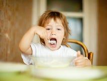 2 ans d'enfant lui-même mange la laiterie Photographie stock libre de droits