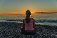 13-15 ans de fille faisant des exercices sur la plage folâtre Images stock
