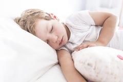 3 ans de garçon d'enfant en bas âge dormant sur le lit avec son coussin préféré photo stock