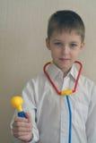 7 ans de garçon en tant que docteur avec des instruments de jouet Images stock
