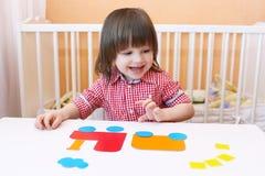 2 ans de garçon ont fait le décolleur des détails de papier Image stock