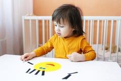 2 ans de garçon relie le visage de personnes des détails de papier Photos libres de droits