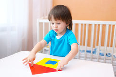 2 ans de petit garçon construisant la maison avec des détails de papier Photographie stock libre de droits