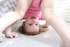 2 ans de petite fille se tient sur la tête dans la tente de tipi Photographie stock libre de droits