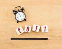 2017 ans sur le cube en bois avec la vue supérieure de crayon et d'horloge sur en bois merci Photographie stock libre de droits
