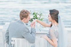 Ansa att önska att kyssa brudens hand på kusten Fotografering för Bildbyråer