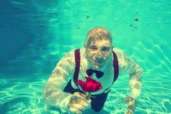 Ansa att erbjuda en undervattens- röd dyk för rospölvatten arkivbild