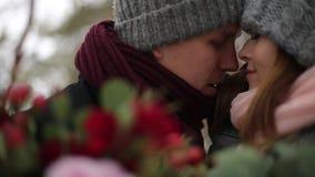 Ansa kommer till bruden, kramar och kysser henne från baksida i snövinterpinjeskog under snöfall romantiskt bröllop