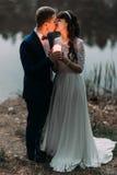 Ansa och hans charmiga nya fru som kysser på kusten av skogsjön på aftonen Royaltyfri Bild