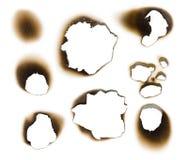 Ansammlung gebrannte Löcher in einem Blatt Papier Stockfotografie