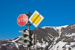 Anschlag! Verkehrsschilder und Ampel auf blauem Himmel Stockbild