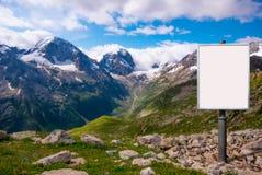 Anschlagtafel für die Werbung angebracht an einer Wiese unter dem Berg stockbilder