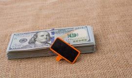 Anschlagtafel gesetzt auf die US-Dollar Banknote Lizenzfreie Stockbilder