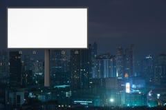 Anschlagtafel mit leerem Raum mit freiem Raum und Gebäude in der Stadt bis zum Nacht stockfotografie
