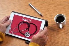 Anschließen an einen Gesundheitsstandort auf Französisch an eine Tablette lizenzfreies stockbild
