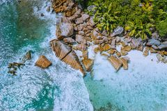 Anse Cocos beach tropical island La Digue Seychelles. Drone aerial view of foam ocean waves rolling towards the rocky royalty free stock photos