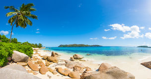 Anse Petite. Beautiful beach Anse Takamaka seen from the granite boulders, La Digue island, Seychelles. Panorama Royalty Free Stock Photo