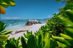Anse Source d`Argent beach - beautifully shaped granite boulder framed by green leaves, La Digue island, Seychelles royalty free stock image