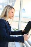 Anseende för affärskvinna i affärsbyggnad med mappen Royaltyfri Fotografi