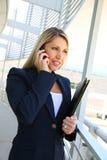 Anseende för affärskvinna, i affärsbyggnad med mappen och samtal på telefonen Fotografering för Bildbyråer