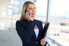 Anseende för affärskvinna, i affärsbyggnad med mappen och samtal på telefonen Royaltyfria Bilder