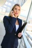Anseende för affärskvinna, i affärsbyggnad med mappen och samtal på telefonen Royaltyfri Bild