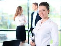 Anseende för affärskvinna i förgrund med en minnestavla i henne händer arkivfoto