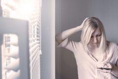 Anseende för affärskvinna nära fönstret och användasmartphonen royaltyfri bild