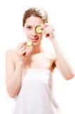 Anseende för flicka Spa för ung härlig kvinna attraktivt med skivor av gurkan i händerna ett stycke på det isolerade ögat royaltyfri fotografi